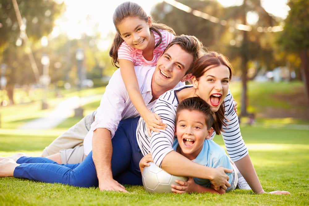 family lying on grass park together