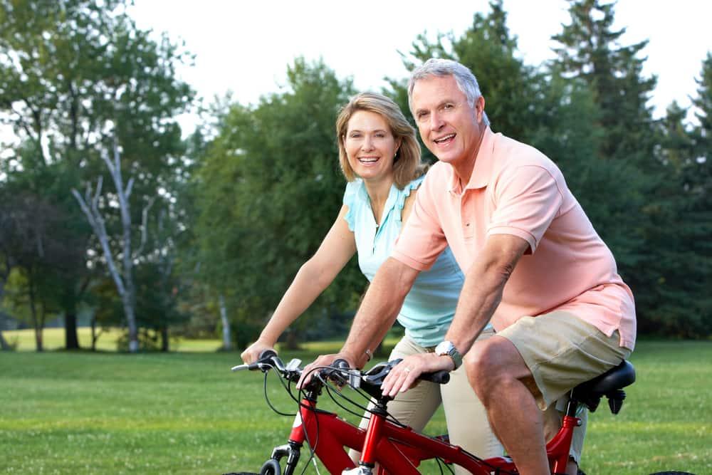 happy elderly senior couple biking in park